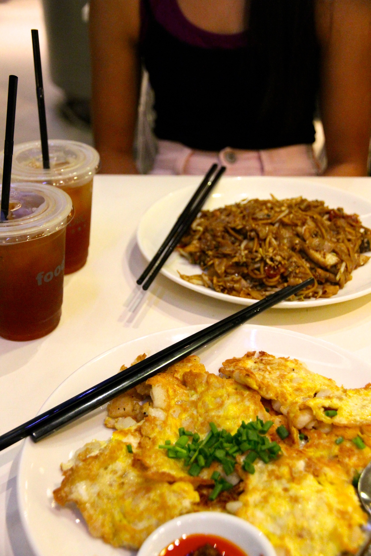 Fried carrot cake in the foreground and Char Kway Teow in the background